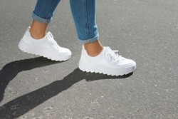 Woman in stylish sneakers walking outdoors, focus on legs