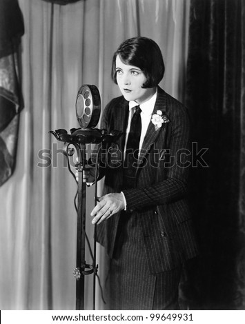 Woman in suit at microphone