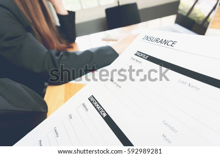 woman in suit in office showing an insurance policy, Concept fill their laptop to get online. #592989281
