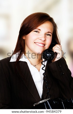 woman in suit on a land line phone