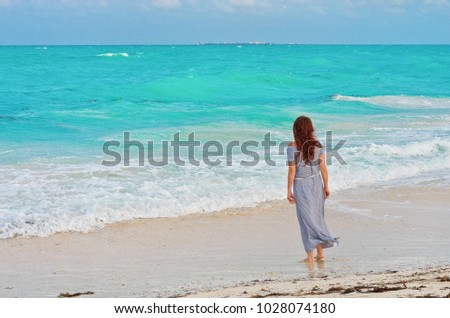 Woman in summer dress looking to the ocean at tropical beach #1028074180