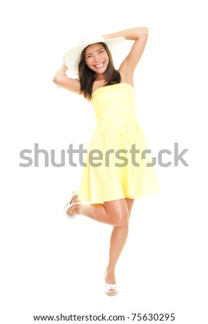 Woman in summer dress playful and cheerful. Isolated on white background in full length. Beautiful fresh young mixed race ethnic female model in yellow dress and summer hat.