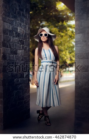 Woman in Summer Dress with Stripes Wearing Sunglasses and Hat - Cute fashion girl in retro inspired outfit