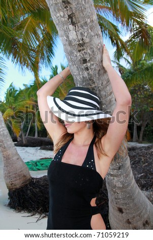Woman in summer hat near palm on beach