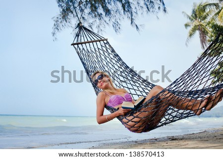 Woman in sunglasses and book relaxing in a hammock
