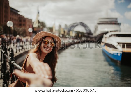 Woman in sunglasses holding boyfriend hand, while taking a photo of her, in Sydney Harbour.