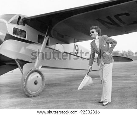 Woman in sunglasses waving a flag on the tarmac next to a airplane - stock photo
