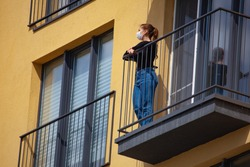 Woman in surgical mask on isolated home balcony of virus protection, coronavirus pandemic, prevention outbreak