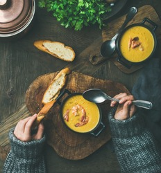 Woman in sweater eating corn creamy soup with shrimps in individual pot, top view. Woman' s hand keeping spoon and bread slice. Flat-lay of rustic dinner table. Slow food, winter warming food concept