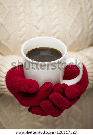 Woman in Sweater with Seasonal Red Mittens Holding a Warm Cup of Coffee.
