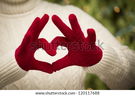 Woman in Sweater with Seasonal Red Mittens Holding Out a Heart Sign with Her Hands.