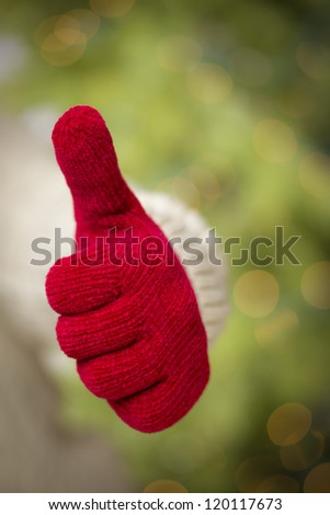 Woman in Sweater with Seasonal Red Mittens Holding Out a Thumb Up Sign with Her Hand.