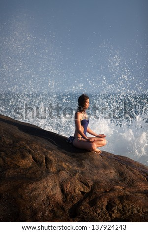 Woman in swimsuit meditates at the sea during sunset against big waves
