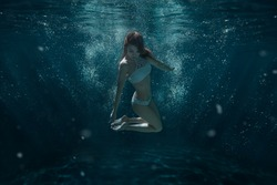 Woman in swimsuit swims under water among the light rays.