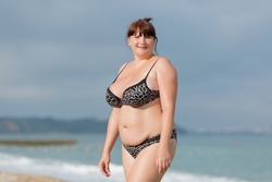 Woman in swimwear at the sea. Overweight young woman in swimsuit against the sea. She looking at camera smiling