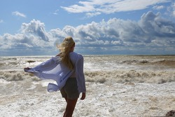 Woman in the blue tunic and shorts is standing on the sea coast and looking at the stormy black sea and heavy clouds. View from the back. Stormy weather on the sea coast. Stormy summer day.