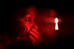 woman in the dark room looks into the keyhole glowing with red mysterious light. She covers her mouth to keep from screaming or being surprised or embarrassment.