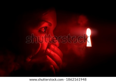 woman in the dark room looks into the keyhole glowing with red mysterious light. She covers her mouth to keep from screaming or being surprised or embarrassment. Stock photo ©