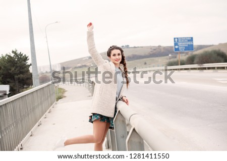 woman in the dress dabbles in sidewalk along the road bridge, there is a transport along the road #1281411550