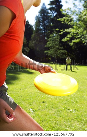 woman in the foreground about to throw a Frisbee disc to a man squatting in the background, grass and line of trees visible in the background