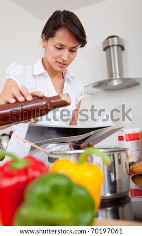 Woman in the kitchen cooking dinner following a recipe