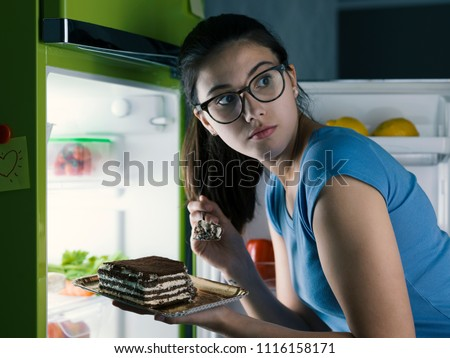Woman in the kitchen having a late night snack, she is taking a delicious dessert from the fridge, diet fail concept #1116158171