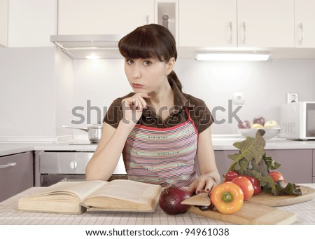 Woman in the kitchen  is reading recipe book - stock photo