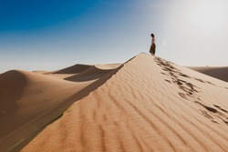 Woman in the middle of the desert, walks on the edge of the dune, tranquility scene, footprints in the sand, blue sky