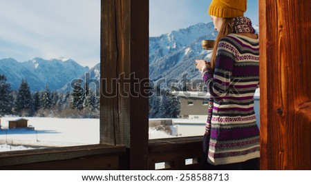Woman in the morning. Young smiling woman enjoying sunny morning in the Alps mountains drinking tea or coffee on a balcony in the chalet house with a mountain view.