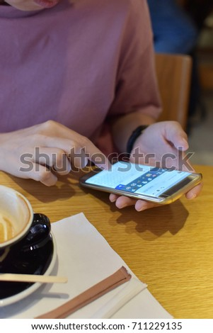 Woman in the office chatting and sending messages with her smart phone.  Businesswoman Smartphone Messaging. Focus on phone, tungsten light tone. #711229135