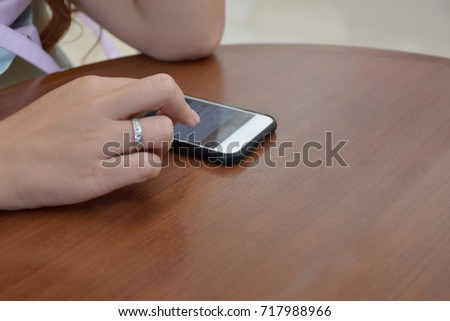 Woman in the office chatting and sending messages with her smart phone.  Businesswoman Smartphone Messaging. Focus on phone.on the table. #717988966