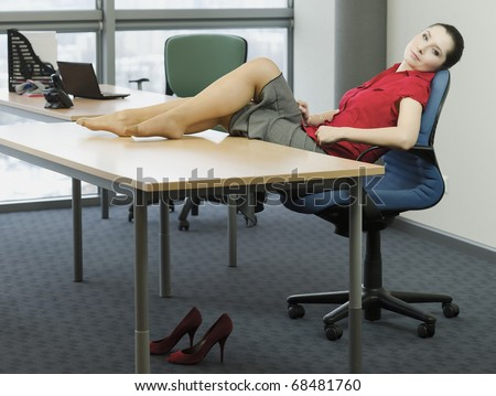 Woman In The Office While Resting With Feet On The Table