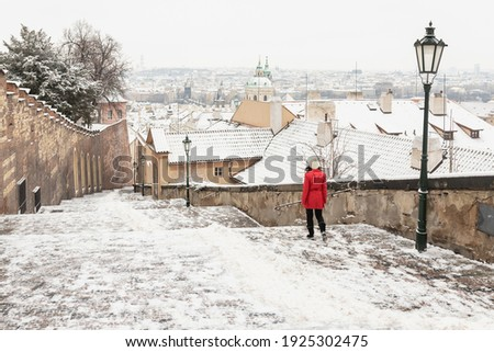 woman in the red coat on New castle stairs cold Nové zámecké schody from Prague castle to old town in the winter Zdjęcia stock ©