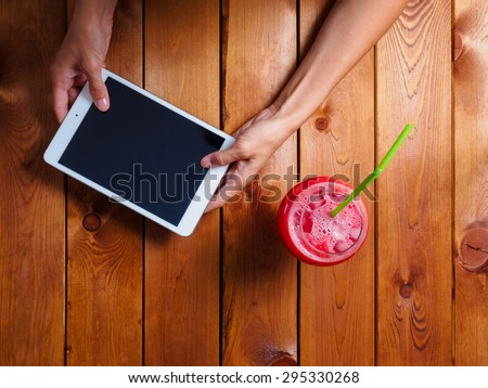 Woman in the restaurant with a cocktail and a tablet