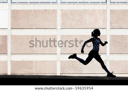 Woman in the shadows of building runs for exercise.