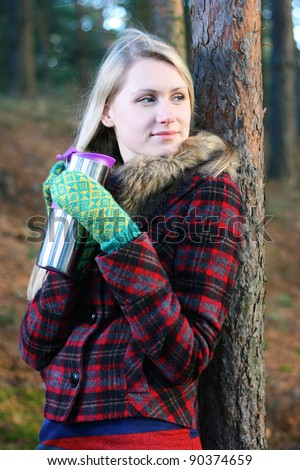 woman in the woods drinking tea from a thermos cup