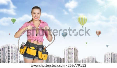 Woman in tool belt with different tools connects two flexible hoses, smiling. Buildings with air balloons as backdrop