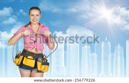 Woman in tool belt with different tools connects two flexible hoses, smiling. Wire-frame buildings as backdrop
