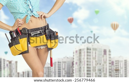 Woman in tool belt with different tools. Hands on hip. Cropped image. Buildings and sky with air balloons on background