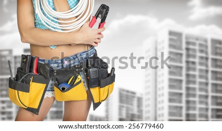Woman in tool belt with different tools holding cable and pliers. Cropped image. Buildings and gray sky as backdrop