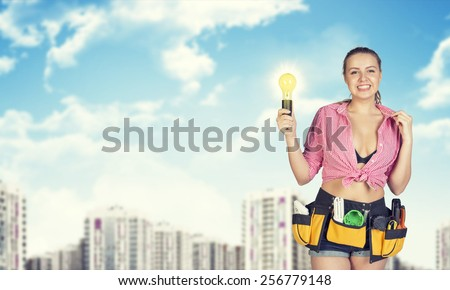 Woman in tool belt with different tools holding light bulb. Blurred buildings in background