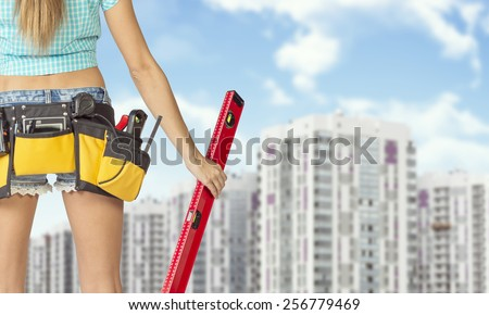 Woman in tool belt with different tools holding red building level. Cropped image. Buildings and sky as backdrop