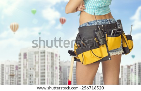 Woman in tool belt with different tools standing backwards, arms crossed. Cropped image. High-rise residential buildings and hot air balloons in background
