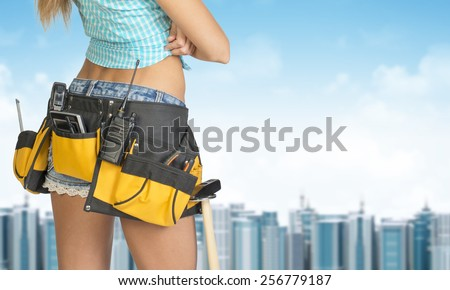 Woman in tool belt with different tools stands back. Cropped image. Building and sky as backdrop