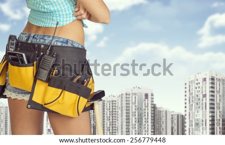 Woman in tool belt with different tools stands back. Cropped image. Buildings and sky as backdrop