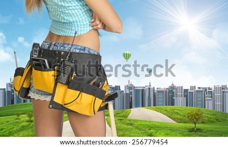 Woman in tool belt with different tools stands back. Cropped image. Green hills with road and buildings on background
