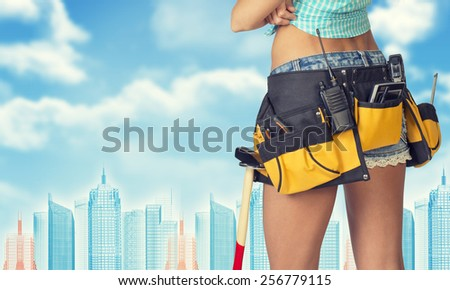 Woman in tool belt with different tools stands back, crossed arms. Cropped image. Wire-frame buildings as backdrop