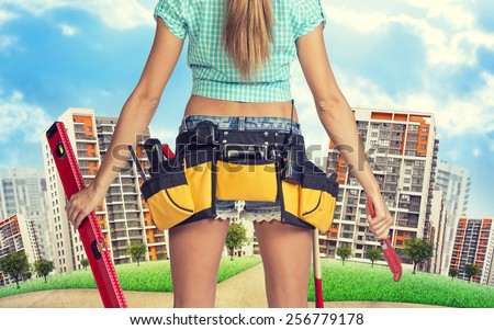 Woman in tool belt with different tools stands back, holding building level and wrench. Cropped image. Green hill with road and buildings on background