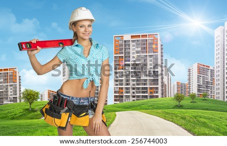 Woman in tool belt with different tools, white helmet, shirt and jeans holding building level on shoulder. Looking at camera, smiling. Green hills with road and buildings in background