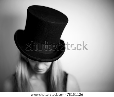 Woman in top hat looking down